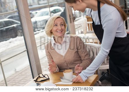 My Aroma Coffee. Inspired Dark-haired Waitress Smiling And Serving Coffee For Her Client