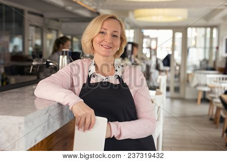 My Working Day. Content Aged Waitress Holding A Tablet And Smiling