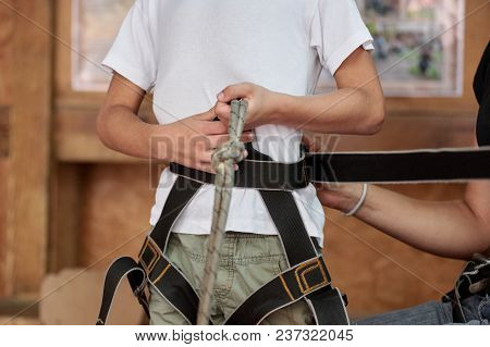 Closeup Of Child Equipped With Safety Straps In Adventure Park