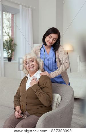 Great Massage. Professional Nurse Giving Massage To Nice Elder Woman Who Sitting On Coach