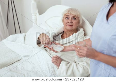 Daily Vitamins. Upset Elder Woman Lying In Bed While Taking Pills