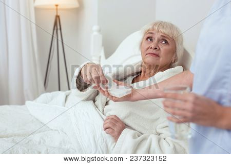 Drugs For Heart. Gloomy Elder Woman Lying In Bed While Stretching For Pills