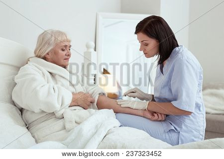 Healthcare Service. Pretty Attractive Nurse Using Syringe While Treating Elder Woman