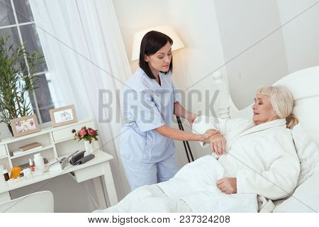 Little Effort. Concentrated Appealing Nurse Helping Elder Woman Who Lying In Bed