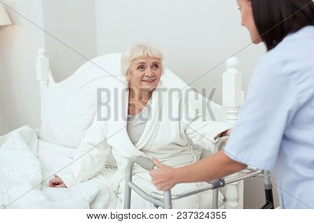 Ready To Go. Positive Cheerful Elder Woman Stretching Hand While Taking Walker