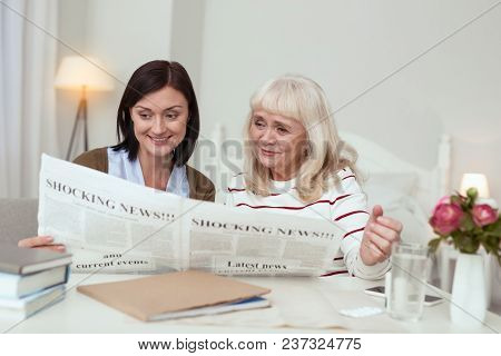 News In World. Satisfied Elder Woman And Caregiver Reading News And Smiling