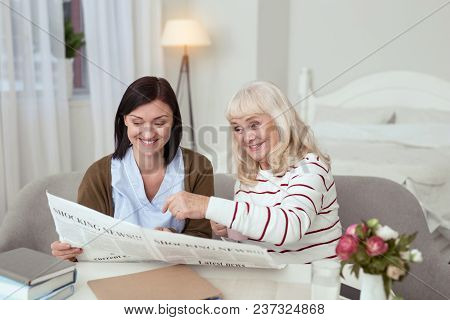 Breaking News. Enthusiastic Elder Woman And Caregiver Reading News And Laughing