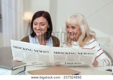 Funny Story. Cheerful Elder Woman And Caregiver Reading News And Chatting