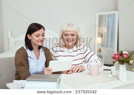 Modern Tablet. Gay Elder Woman And Caregiver Using Tablet While Smiling