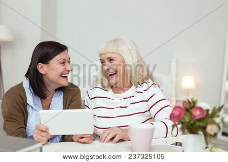 Innovative Technology. Positive Elder Woman And Caregiver Using Tablet While Laughing