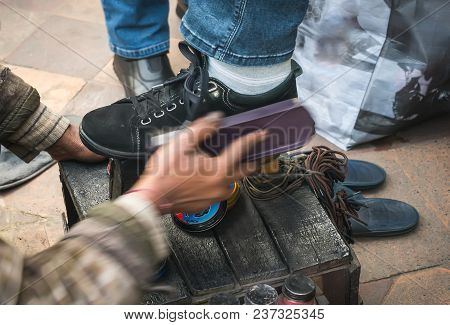 Indian man cleaning customer shoes on city pavement. new Delhi India. Brushing brush your black shoes with black cream. poster