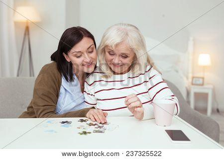 Weekend Together. Joyful Elder Woman And Caregiver Embracing While Gathering Puzzle