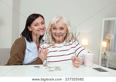 Brain Activity. Enthusiastic Elder Woman And Caregiver Looking At Camera While Gathering Puzzle
