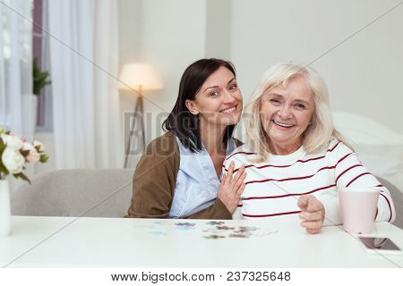 Exercise For Brain. Pleased Elder Woman And Caregiver Laughing While Gathering Puzzle