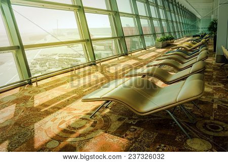 Soft Comfortable Sunbeds In The Airport Waiting Room In Front Of The Panoramic Window