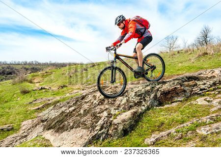 Cyclist in Red Jacket Riding the Mountain Bike Down Rocky Hill. Extreme Sport and Adventure Concept.