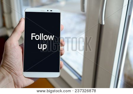 A Person Sees A White Inscription On A Black Smartphone Display That Holds In His Hand. Follow Up