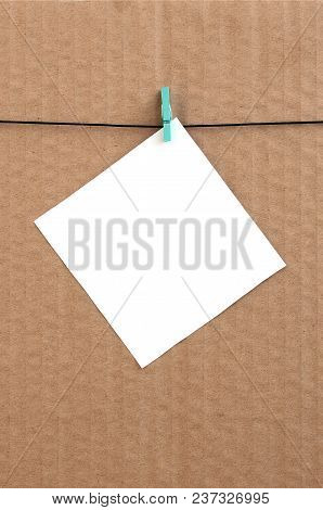 White Blank Card On Rope On A Brown Cardboard Background. Creative Reminder, Small Sheet Of Paper On