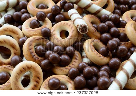 A Lot Of Crispy Sweet Tubules, Chocolate Melting Balls And Yellow Bagels Lie On A Wooden Surface. Cl