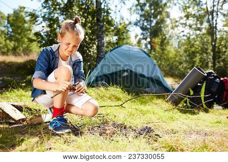 Little boy going to make bonfire on green grass not far from his tent in the forest during backpack trip