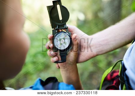 Hands of boy scouts holding compass with arrow pointing north while looking for their camp