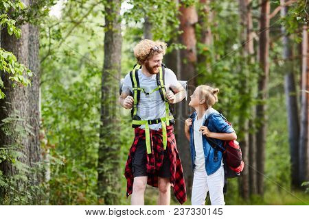 Two friendly boy scouts with backpacks walking in the forest and having talk on their way to camp