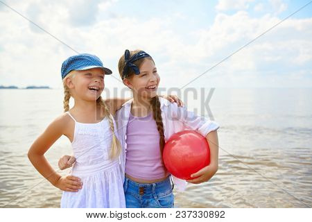 Two laughing girlfriends with red ball standing on sandy beach while spending weekend by seaside
