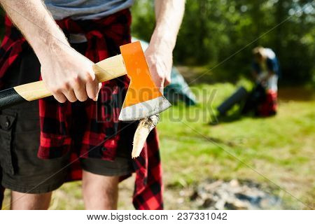 Young tripper with axe sharpening edge of wooden stick before making bonfire to prepare food