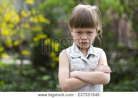 Pretty Funny Moody Little Blond Preschool Girl In White Sleeveless Dress Looks Into Camera Feeling A