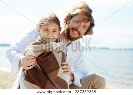 Happy young man and his little daughter enjoying windy summer day by seaside