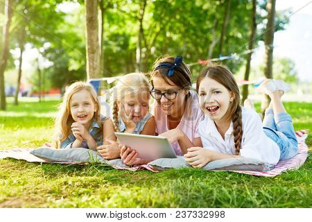 Happy little girls and their teacher with tablet spending weekend in park by watching movie or videos in the net