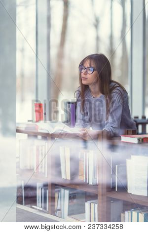 Young woman with books in the library