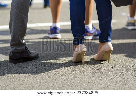 Close Up Of Men And Women Legs In Different Shoes, High Heels Walking Fast Along The Concrete Road O