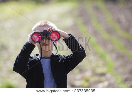 Portrait Of Little Cute Handsome Cute Blond Boy Watching Intently Something Through Binoculars In Di