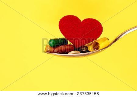 The Colorful Medical Supplement And Drug Pills With Red Heart In Spoon On Yellow Background , Pharma