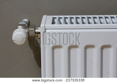 White Heating Radiator With Thermostat Valve On Wall In An Apartment Interior After Renovation Works