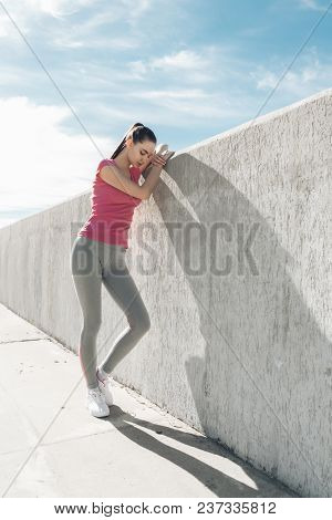 A Slender Strong Girl Resting After Training Outdoors, Doing Sports And Fitness