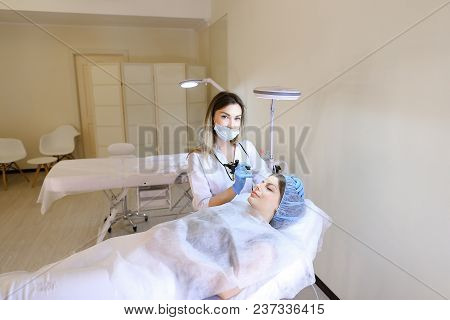 Nice Cosmetologist Doing Tattooing Procedure For Female Person At Cabinet. Concept Of Beauty Salon A