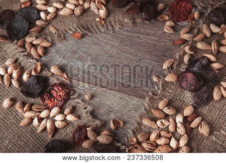 Organic Food Amonds, Raisins, Dried Apricots, Dried Tomatoes, Prunes, Dried Fruits, In Wooden Table.