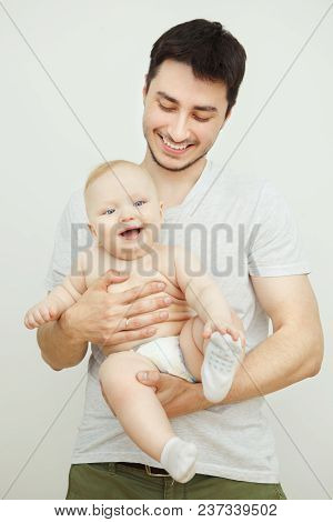 Father Posing With His Little Son In Pants And Socks.