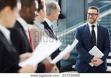 Successful businessman in elegant formalwear standing in front of business team with papers and listening to their reports at briefing