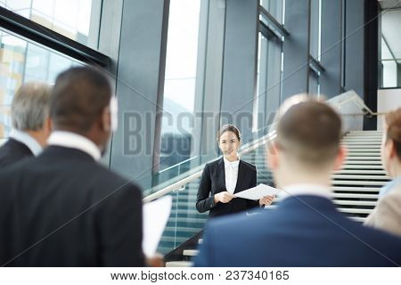 Young businesswoman making report in front of audience at business briefing in airport lounge