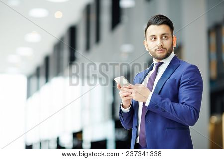 Young elegant businessman in formalwear texting in smartphone while waiting for client or colleague