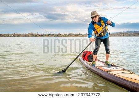 senior man on expedition stand up paddleboard with a large waterproof duffel on deck, a lake in Colorado
