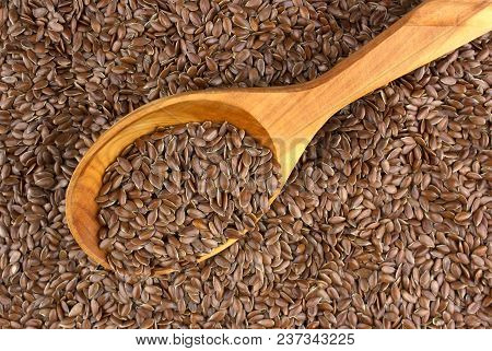 Flax Seeds In Wooden Spoon On Background.  Also Known As Linseed, Flaxseed And Common Flax. Pile Of