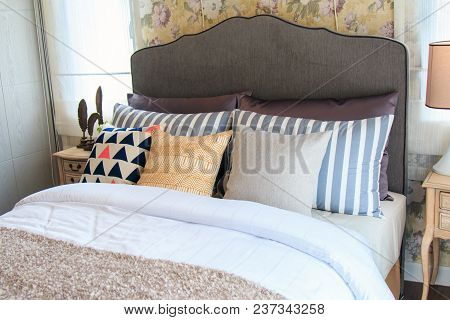 An Interior Design Bedroom With Colorful Pillows Learning Against Brown Headboard And Modern Lamp On