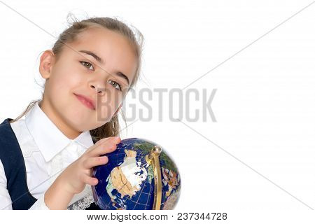 Beautiful Little Schoolgirl Girl Studying A Globe On A White Background. The Concept Of Teaching Geo