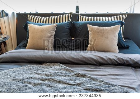 Black And Brown Pillows Learnind Against Headboard And Classic Lamp On Table With Frames On White Wa