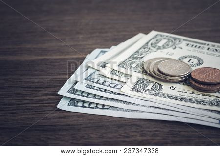 Money Banknotes Us Dollar And Cash Coins Put On Wooden Table, Dark Vintage Style. Currency, Payment,