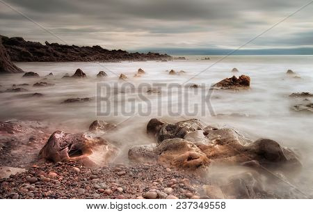 A Long Exposure Used To Calm A The Sea On The Beautiful Rocky Coastline Of Rotherslade Bay, A Small